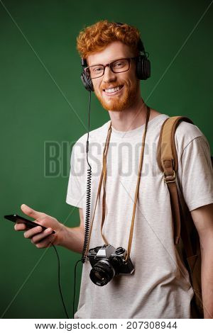 Smiling readhead bearded hipster with backpack and retro camera, listening to music, looking at camera, over green background