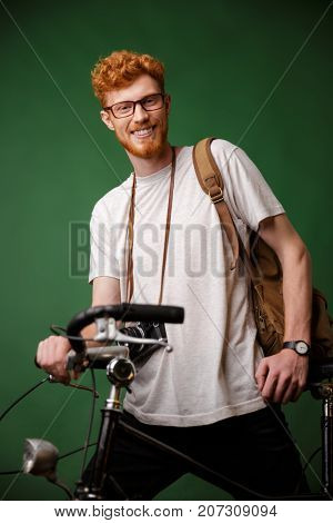 Young cheerful readhead bearded hipster with backpack and retro camera, standing on bicycle isolated over green background