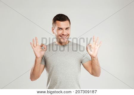 Picture of happy young man dressed in grey t-shirt isolated over grey wall background showing okay gesture. Looking at camera.