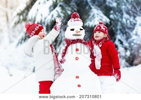 Kids Building Snowman. Children In Snow. Winter Fun.