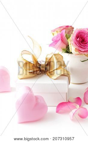 gift box tied with pink ribbon bow, rose flowers. white background