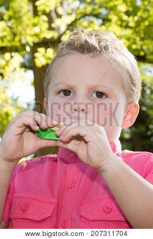 Blond Boy Child Eating A Fruit Compote In A Gourd