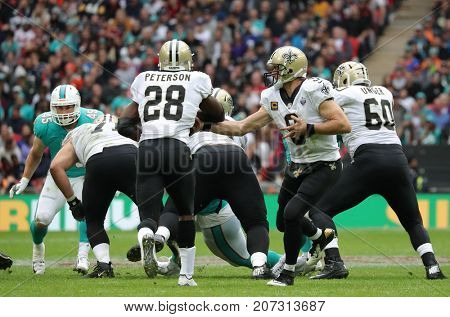 LONDON, ENGLAND - OCTOBER 01: quarterback Drew Brees (9) hands off to  running back Adrian Peterson (28) during the NFL match between the Miami Dolphins and the New Orleans Saints at Wembley Stadium