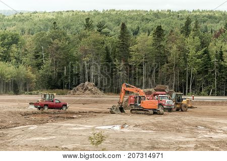 Clearcut forest deforest with machines trucks excavator in New Brunswick Canada