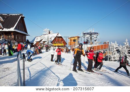 KOHUTKA SKI RESORT, CZECH REPUBLIC - JANUARY 16, 2010: Ski resort in the Czech Tatra mountains. Lodges with peaked roofs. Frosty sunny winter day. Skiers in bright jackets prepare for descent on skis