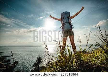 Tourist with backpack standing on sea coast with raised hands