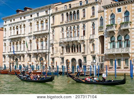 VENICE,ITALY - JULY 26,2017 : Gondolas next to old beautiful palaces at the Grand Canal In Venice