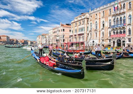 VENICE,ITALY - JULY 26,2017 : Traditional gondolas next to old beautiful palaces at the Grand Canal In Venice