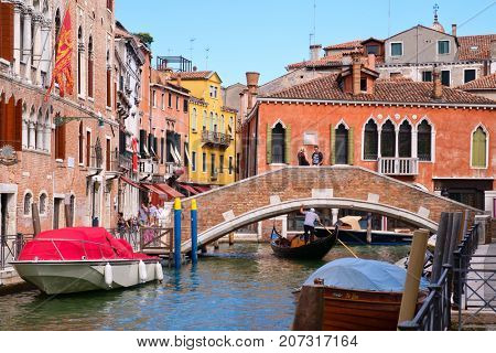VENICE,ITALY - JULY 26,2017 : Gondola on a narrow canal surrounded by old buildings in Venice