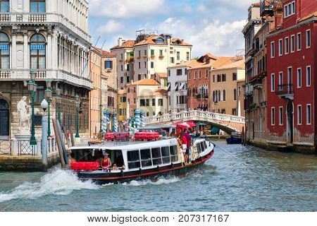 VENICE,ITALY - JULY 28,2017 : Vaporetto or water bus on a canal in Venice surrounded by old colorful palaces