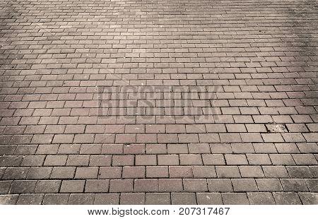 Grey brick stone street road perspective. Pavement texture