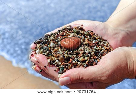 Small pebbles in hands on sea shore background