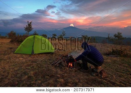 man warms on the campfire at dusk. On background the tent and Etna Volcano from Nebrodi Park, Sicily