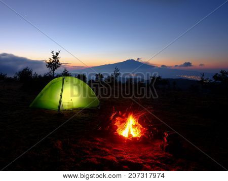 lighting tent, campfire and Volcano Etna at dawn from Nebrodi Park, Sicily