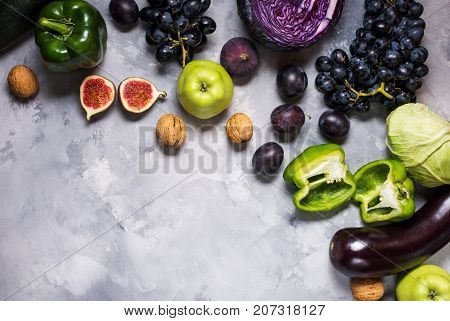 Fresh organic raw green and purple colored vegetables and fruits on stone background. Top view. Copyspace