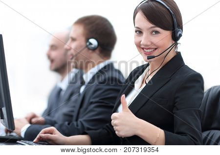 Manager of the call centre shows thumb up sitting at your Desk