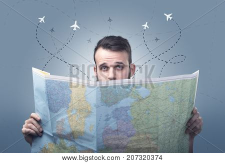 Handsome young man holding a map with little planes and their paths above him