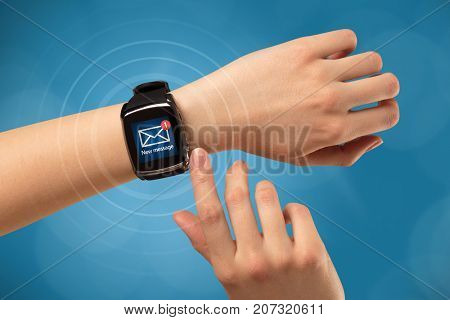 Female hand receives new message on her smartwatch