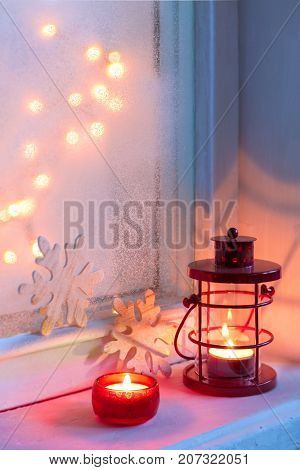 Red Christmas lantern and candle in dusk on old windowsill.