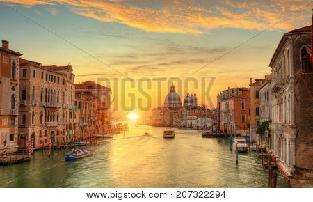 Beautiful sunrise in Grand canal with Church of Santa Maria della Salute on background, Venice, Italy, European Union. Famous historical heritage.