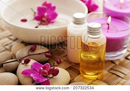 massage oil bottles, aromatherapy candles, pebbles and flowers