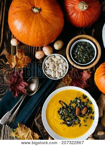 Autumn pumpkin soup with pumpkin seeds and almond, shot from above rustic wooden table