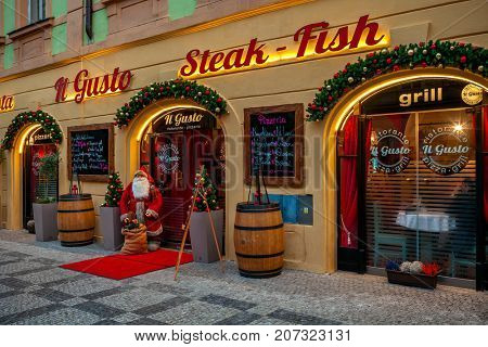 PRAGUE, CZECH REPUBLIC - DECEMBER 10, 2016: Decorative Santa Clause at the entrance to Christmas decorated restaurant Il Gusto - popular italian restaurant at Stare Mesto (Old Town) in Prague.