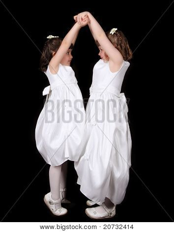 Playful Twin Sisters In White Gowns With Hands Joined In The Air