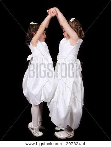 Dos hermanas gemelas juguetón en vestidos de blancos con las manos juntas en el aire