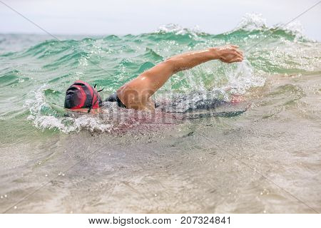 Swimmer swimming crawl freestyle in ocean wave during triathlon swim race. Man triathlete doing watersport workout swimming in sea water. Male triathlete in professional triathlon outfit.