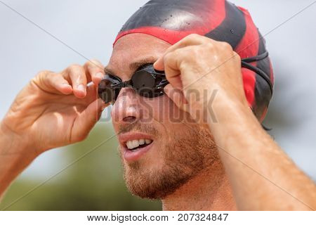 Triathlon swimmer athlete going swimming. Male triathlete swimmer putting swim goggles getting ready for an ocean swim. Fit man in professional triathlon suit training for ironman on Hawaii.