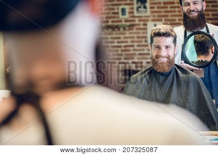 Over the shoulder view of a handsome young man smiling while looking at his new trendy haircut, in the mirror held by his experienced barber in a cool hair salon