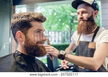 Dedicated male hairstylist using scissors and plastic comb while giving a cool haircut to a redhead bearded young man in a trendy beauty salon
