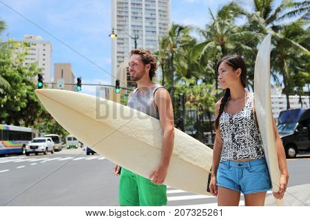 Honolulu Hawaii lifestyle surfers people walking in city with surfboards going to the beach surfing. Outside hawaiian surf living. Surfer couple crossing street. Waikiki, Honolulu, Oahu, Hawaii, USA.