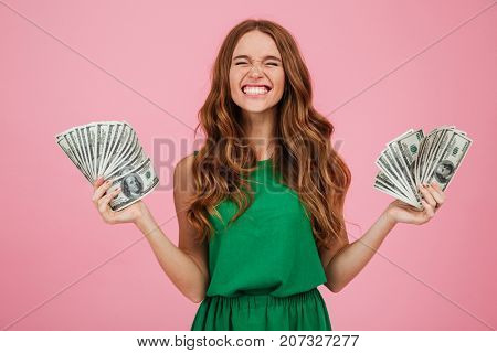 Portrait of a satisfied happy woman winner with long hair holding bunch of money banknotes in each hand isolated over pink background