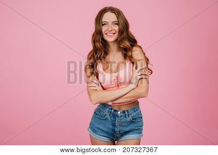 Portrait of a smiling pretty woman standing with arms folded and looking at camera isolated over pink background