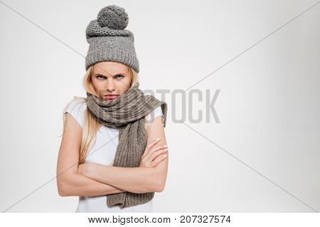 Portrait of an upset unsatisfied woman in winter hat and scarf standing with arms folded and looking at camera isolated over white background