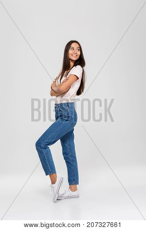 Full length portrait of a smiling cute asian woman standing and looking away at copy space isolated over white background