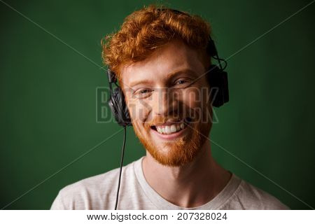 Young readhead man listening music in headphones, looking at camera, over green background