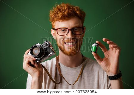 Close-up shot of young readhead bearded hipster holding retro photocamera and camera roll, over green background