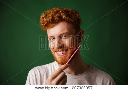 Close-up shot of smiling readhead man, combing his beard with pink comb, over green background