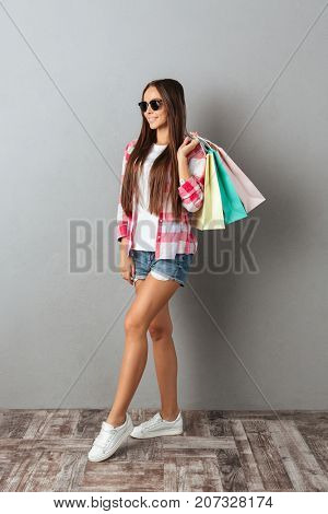 Full length portrait of a smiling woman in casual wear, holding shopping bags over gray wall