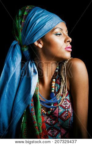 African black young woman beauty portrait with turban headscarf and traditional colorful clothes studio shot