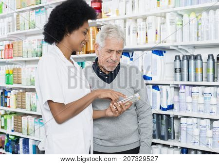Pharmacist Showing Information On Product To Customer
