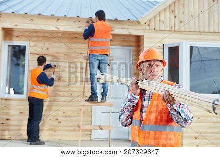 Craftsman carrying wood and working with carpenters on new house