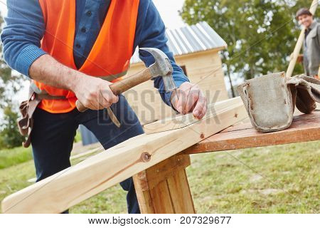 Craftsman working with hammer at new building's construction site