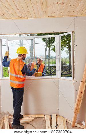 Skilled window fitters assembling window in teamwork
