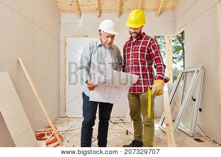 Master and craftsman renovating woodhouse and planning