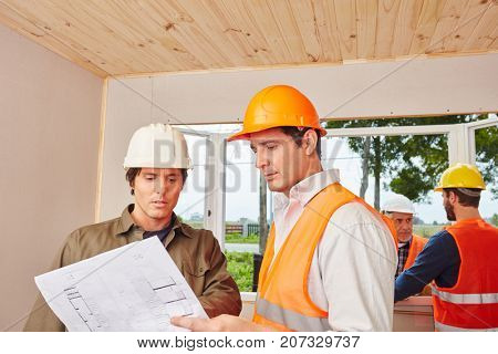 Architect and craftsmen working using floorplan for planning