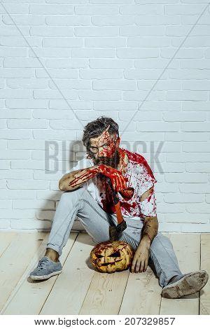 Halloween Man Sitting With Pumpkin And Axe On Wooden Floor